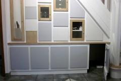 Agencement sous escalier, bois composite et chêne, finition laquée sur mesure et vernis chêne clair.