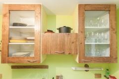 Cuisine partiellement en palettes récupérées, finition vernis brillant chêne foncé.