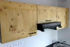 cuisine en bois composite laqué noir sur mesure et façades 100% récup en palettes, finition huile teintée miel.